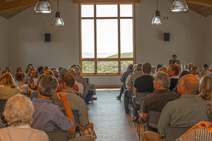 audience inside center enjoys the view through the floor-to-ceiling picture window